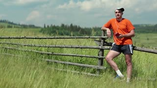 Adult man in orange t-shirt with a red smartphone stands in the field and listens to music. Man listens to the radio