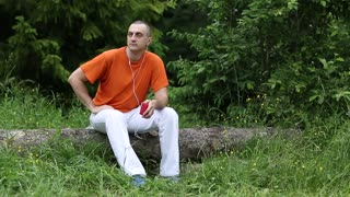 Adult man in orange t-shirt with red smartphone sits on a fallen tree in the forest and listens to music. Music lover