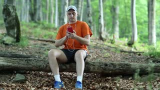 Adult man in orange t-shirt with red smartphone sits on a fallen tree in the forest. Man with smartphone and earphones. Male with cell phone