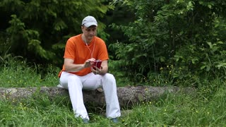 Adult man in orange t-shirt with red smartphone sits on a fallen tree in the forest