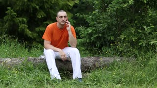 Adult man sits on a fallen tree in the forest and communicates via smartphone. Man in orange t-shirt with a cell phone sits on a fallen tree in the forest