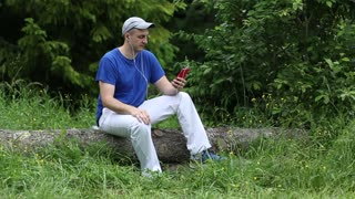 Adult man with red smartphone sits on a fallen tree in the forest. Man with smartphone communicates through skype