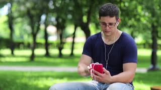Adult man with red smartphone sits on the bench in public garden. Man in blue t-shirt sits on the bench in city park and uses cell phone. Man uses red personal mobile phone with earpieces