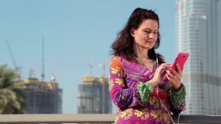 Adult woman stands near skyscraper and communicates via red smartphone. Businesswoman with cell phone. Woman stands near megatall skyscraper and talks through skype