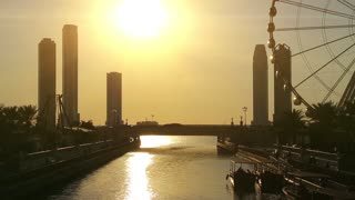 Al Qasba canal and ferris wheel in Sharjah city, United Arab Emirates. Sharjah - third largest and third most populous city in UAE, and the capital of the emirate of Sharjah. Sunset in Sharjah, UAE