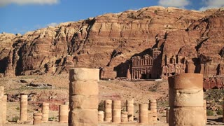 Ancient columns of Great Temple or Temple of Winged Lions in Petra - historical and archaeological rock-cut city in Hashemite Kingdom of Jordan. Royal Tombs carved in the mountain on the background