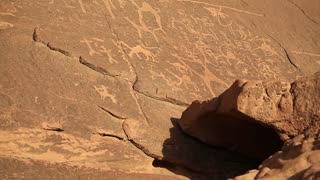 Ancient rock paintings, petroglyphs depicting humans and camels on the rock in Wadi Rum desert, Hashemite Kingdom of Jordan