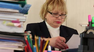 Angry senior woman bookkeeper with glasses tears commercial papers