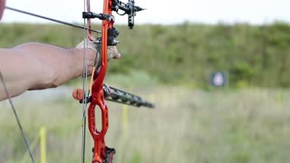 Archer shoots a bow at a target. Man holds bow in his left hand
