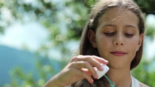 Attractive girl blowing soap bubbles. Female with soap bubbles