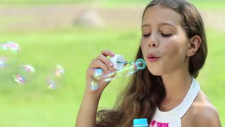 Attractive girl blowing soap bubbles on the meadow