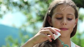 Attractive girl blowing soap bubbles