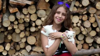 Attractive girl holds in hands three little kittens. Beautiful girl in blue sunglasses holds in hands two white and one black cats. Girl with kittens near stack of firewood