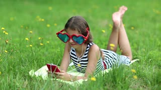Attractive girl in big sunglasses in the shape of hearts with red smartphone lies on the grass. Pretty girl playing the game on his smartphone. Girl in glasses lies on green grass and uses cell phone