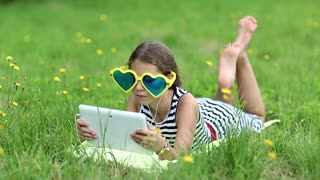 Attractive girl in big sunglasses with tablet computer lies on green grass. Little girl in glasses lies on the green grass and uses tablet pc. Girl playing the game on his tablet computer