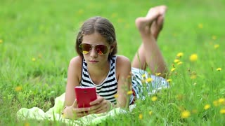Attractive girl in sunglasses with red smartphone lies on the grass. Pretty girl playing the game on his smartphone. Little girl in glasses lies on the green grass and uses cell phone