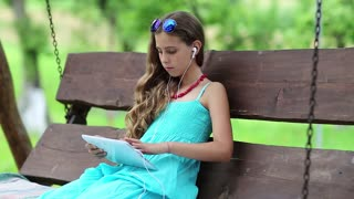 Attractive girl sits on swing bench and holds in hands tablet computer. Pretty girl with tablet pc sits on bench in garden. Girl playing the game on his tablet computer. Beautiful girl with tablet pc