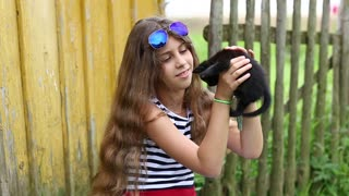 Attractive girl with black cat. Pretty girl holds in hands black little kitten. Girl caressing and stroking a cat