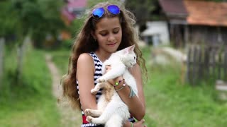 Beautiful girl holds in hands white cat and looks at the camera. Girl in blue sunglasses holds in hands white cat. Unique cat has one blue eye and one yellow eye, it is seen in high resolution video