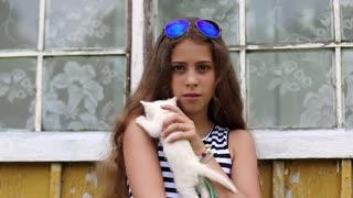 Beautiful girl holds in hands white little cat. Attractive girl in blue sunglasses holds in hands white kitten. Girl kissing cat