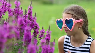 Beautiful girl in big glasses in the shape of hearts near purple flowers. Girl in big sunglasses smells flowers