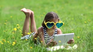 Beautiful girl in big sunglasses in shape of hearts with tablet computer lies on the grass. Girl playing the game on his tablet computer. Little girl in glasses lies on green grass and uses tablet pc
