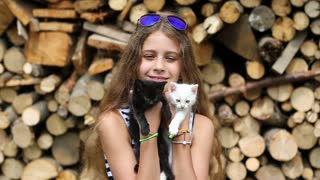 Beautiful girl in blue sunglasses holds in hands white and black cats. Attractive girl holds in hands two little kittens. Girl with kittens near stack of firewood