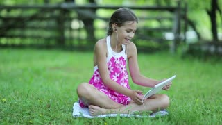 Beautiful girl in pink dress with tablet computer sits on green grass in garden. Little girl with tablet pc sits on the grass in garden. Girl communicates through Skype. Female with tablet computer