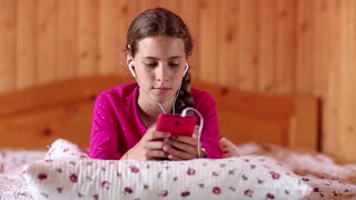 Beautiful girl lies on the bed and communicates via smartphone. Beautiful girl lies on the bed and uses his smartphone. Female with smartphone communicates through skype. Girl lies on the sofa