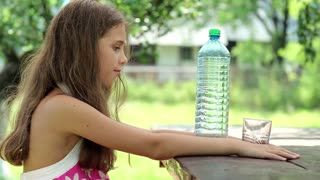 Beautiful girl pours water from a bottle into a glass