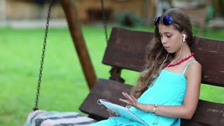 Beautiful girl sits on swing bench and holds in hands tablet computer. Pretty girl with tablet pc sits on bench in garden. Girl playing the game on his tablet computer. Beautiful girl with tablet pc