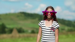 Beautiful girl stands on meadow and sings a song. Pretty girl in big glasses in the shape of stars sings a song and dance