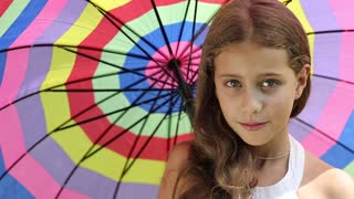 Beautiful girl with colorful umbrella looking into the camera