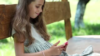 Beautiful girl with red smartphone sits on the bench. Nice girl with red cell phone sits on the bench. Girl playing the game on his smartphone