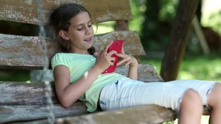 Beautiful girl with red smartphone sits on the swing bench. Little girl with cell phone sits on the bench in garden. Girl communicates via mobile phone. Attractive girl uses smartphone
