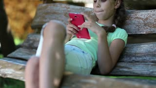 Beautiful girl with red smartphone sits on the swing bench. Little girl with cell phone sits on the bench in garden. Girl communicates via mobile phone. Pretty girl uses his smartphone