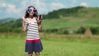 Beautiful girl with smartphone stands on the meadow, listens to music, dances and sings a song. Girl in big glasses with smartphone listens to music and dances on green lawn, and also sings a song