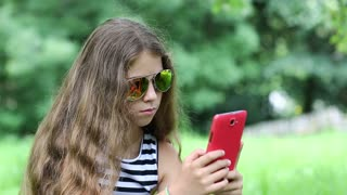 Beautiful girl with sunglasses makes selfie on his smartphone. Attractive girl with red cell phone makes photos. Female makes photos on red smartphone