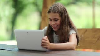 Beautiful girl with tablet computer sits on the bench in summerhouse. Girl playing the game on his tablet computer. Little girl with Tablet-PC sits on the bench in bower