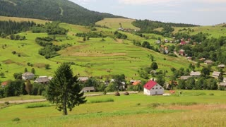 Beautiful green hills and cottage with red roof in village, Ukraine