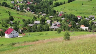 Beautiful green hills and cottage with red roof in village