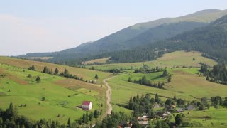 Beautiful green hills and cottage with red roof near village