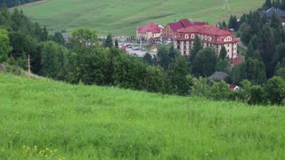 Beautiful green meadows and hotel building with red roof