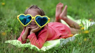 Beautiful little girl in big sunglasses lies on the grass. Funny little girl in glasses lies on the green grass and looks at the camera