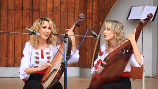 Beautiful twin sisters in national costume playing bandura (Ukrainian string instrument)