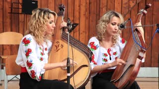 Beautiful twin sisters in national costume sing and play on bandura (Ukrainian string instrument)