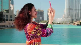 Beautiful woman stands near blue pool and makes photos on his smartphone. Female makes photos by the use of smartphone. Woman makes photos of Burj Khalifa in Dubai, United Arab Emirates
