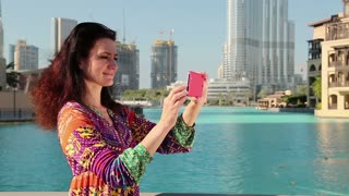 Beautiful woman stands near blue pool and makes photos on his smartphone. Female makes photos on his smartphone. Woman makes photos of Burj Khalifa megatall skyscraper in Dubai, United Arab Emirates
