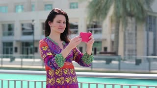 Beautiful woman stands near the blue pool and makes selfie on his smartphone. Female makes photos on his smartphone. Businesswoman with smartphone. Adult woman uses red smartphone, Dubai, UAE