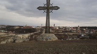 Big metal cross in Kamianets-Podilskyi city in western Ukraine. On the background - old city of Kamianets-Podilskyi, located in historic region of Podolia